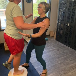 Ability Physical Therapy Owner Lori Swanton assists a client with her balance.